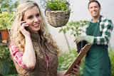 Smiling blonde woman phoning in a green house