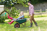 Handsome man pushing his laughing girlfriend in a wheelbarrow