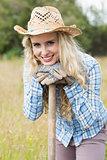 Smiling blonde woman leaning on a shovel wearing gardening gloves