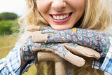 Cheerful blonde woman leaning on a shovel wearing gardening gloves