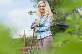 Cheerful blonde woman standing in her garden