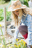 Smiling blonde woman working in the garden