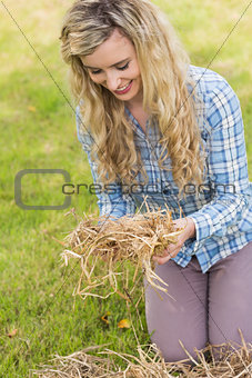 Smiling blonde feeling yellow straw