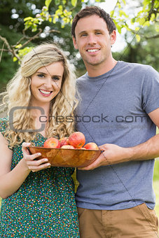 Young couple holding a bowl with apples