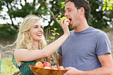 Blonde woman feeding her boyfriend with an apple
