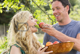 Young man feeding his girlfriend with an apple