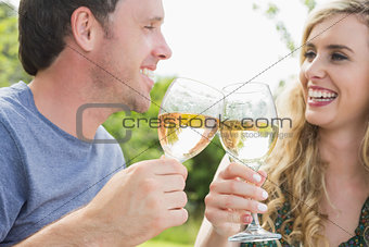 Cheerful couple toasting with white wine