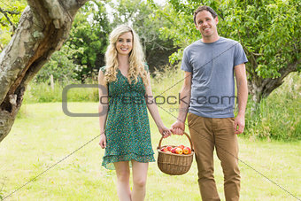 Smiling couple carrying a basket of apples