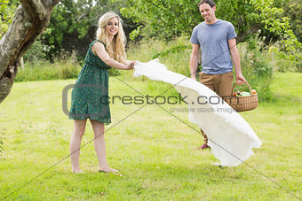 A woman spreading a blanket for a picnic with her boyfriend