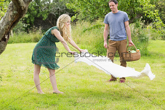 Blonde woman spreading a blanket for a picnic with her boyfriend