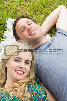 Smiling couple lying on a blanket