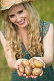 Blonde young woman handing some potatoes