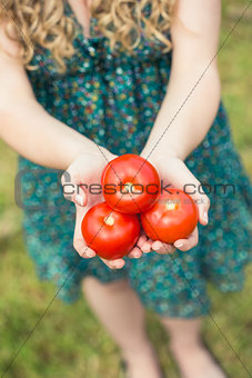 Blonde woman holding some tomatoes