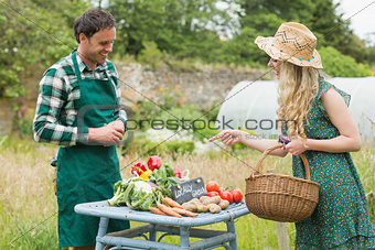 Beautiful blonde woman buying vegetables at farmers market