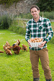 Happy man showing a basket filled with eggs