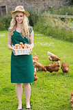 Smiling pretty woman presenting a basket filled with eggs