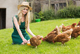 Young pretty blonde feeding her chickens smiling at camera