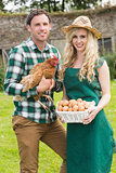 Happy young couple holding chicken and basket of eggs