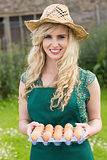 Young smiling blonde woman holding carton of eggs