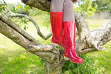 Woman wearing red rubber wellington boots sitting on a tree
