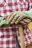 Gardener wearing check shirt leaning on a shovel