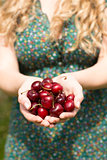 Close up of a blonde woman holding some cherries