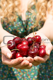 Close up of a blonde woman showing some cherries