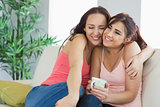 Two embracing women sitting on a couch