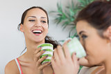 Young laughing woman having coffee with friend