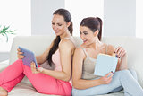 Beautiful woman showing her tablet to her friend