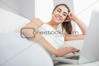 Smiling brunette woman typing at a laptop
