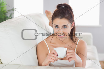 Beautiful woman lying on a couch holding a cup