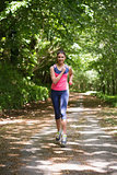 Lovely young woman jogging towards camera