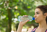 Sporty woman drinking water outdoors
