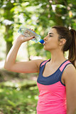 Handsome brunette woman drinking water
