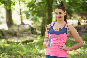 Fit cute woman wearing sportswear holding bottle