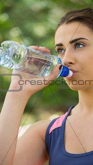 Fit cute woman wearing sportswear drinking from bottle