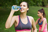 Cute fit woman wearing sportswear drinking water