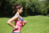 Fit woman running in the sunshine and smiling