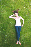 Cute brunette woman lying on a lawn