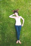 Cute brunette woman lying on a lawn