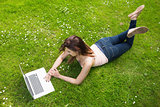 Pretty young woman lying on a lawn using her laptop