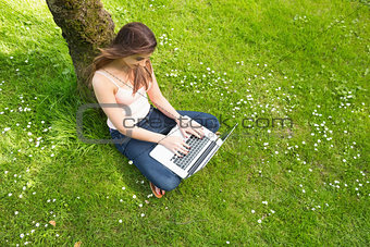 Cute woman leaning against a tree using her notebook