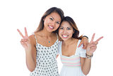 Two smiling young women making a peace gesture