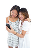 Two happy asian women using a smartphone