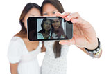 Two smiling asian sisters taking a self portrait