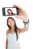 Smiling asian woman taking a selfie