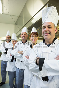 Team of happy chefs smiling at the camera