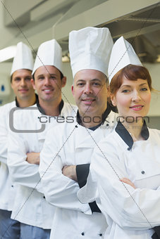 Four happy chefs smiling at the camera
