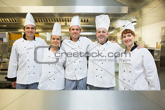 Five happy chefs smiling at the camera